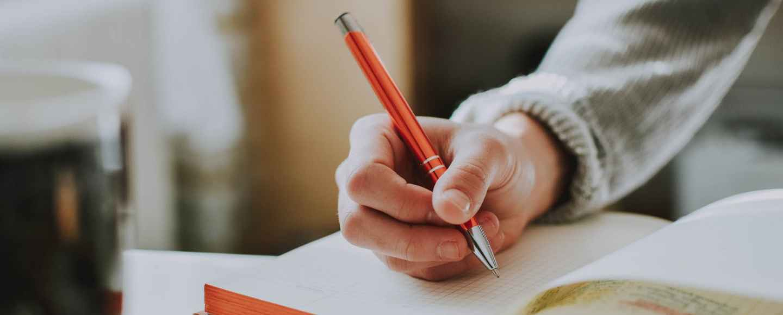 person holding orange pen