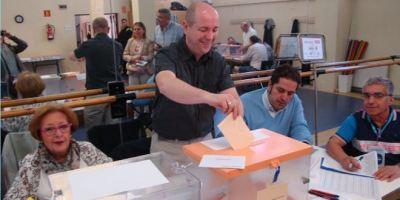 El presidente de una mesa electoral introduce un sobre en una de las urnas.