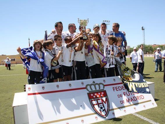 Campeones del año pasado exhiben su copa.