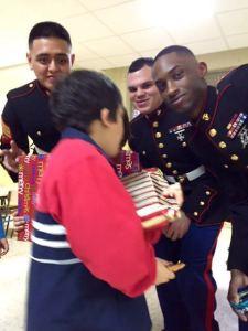 Los Marines entregan un regalo a un niño.