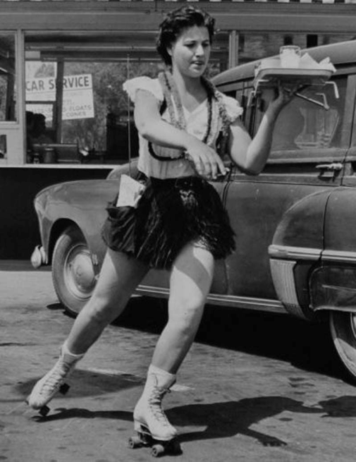 Female car hop roller skating at 1950s drive in restaurant