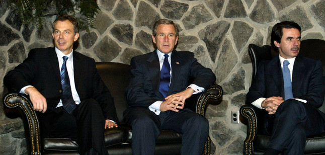 British Prime Minister Tony Blair (L), U.S. President George W. Bush (C) and Spanish Prime Minister Jose Maria Aznar meet at Lajes Field in the Azores, March 16, 2003. The meeting was portrayed as a final diplomatic push for a U.N. resolution demanding that Iraq disarm or face attack. Bush said on Sunday he believed the United Nations must have a role in rebuilding Iraq after the removal of President Saddam Hussein. REUTERS/Kevin Lamarque