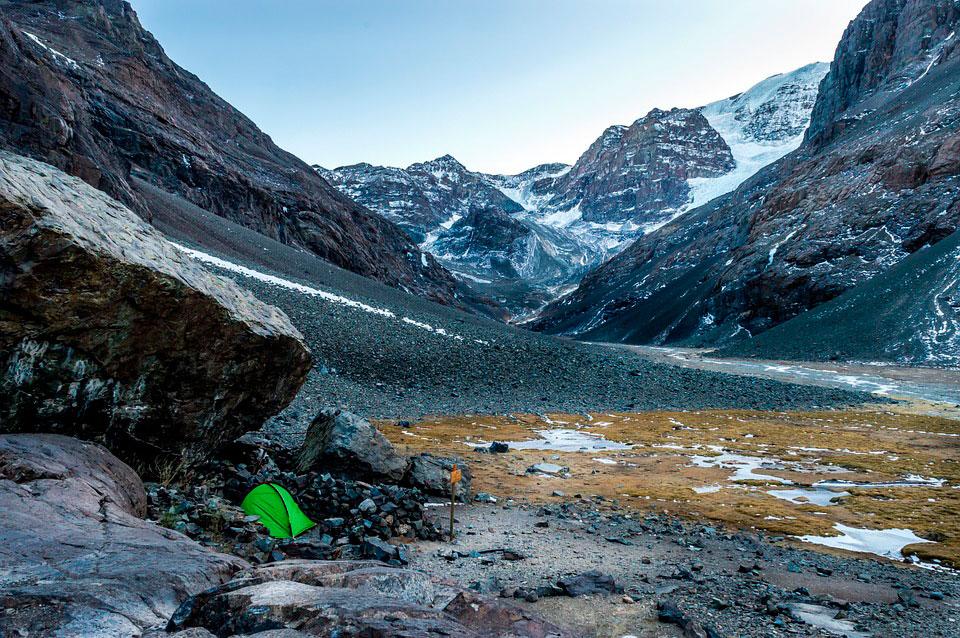 Carpa mochileros verde fluorescente en un paisaje de alta montaña