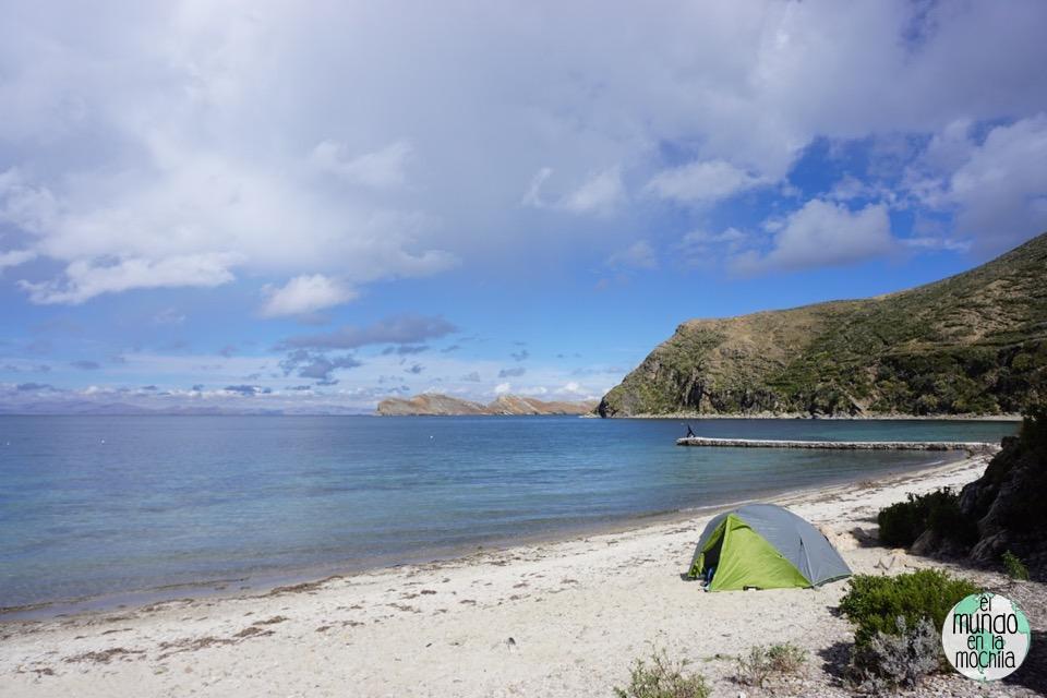 Nuestra tienda de campaña, la Kelty TN2, en una playa del Titicaca. Gaby hace yoga en el muelle.