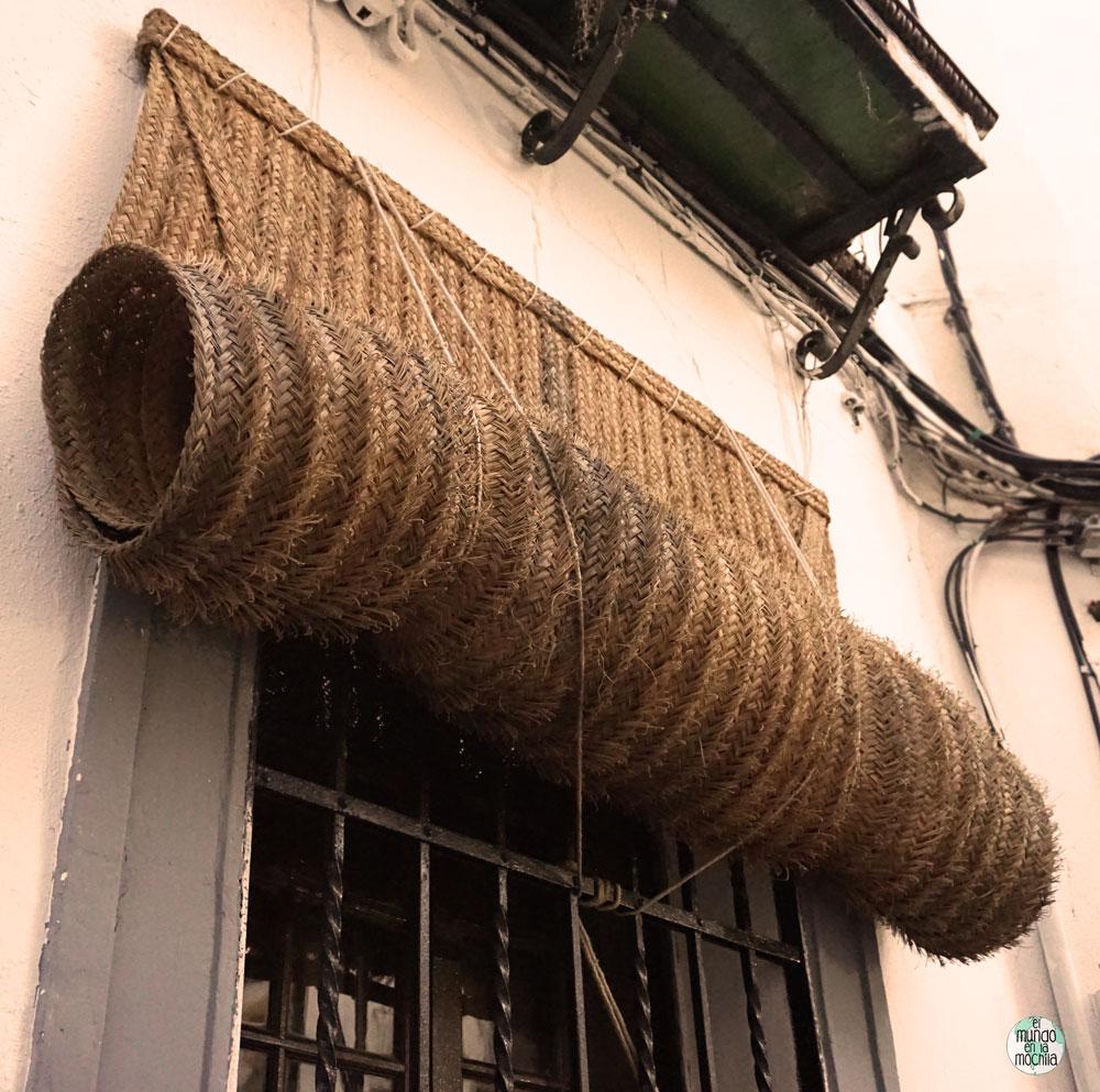Cortina de esparto enrollada fuera de una ventana en Córdoba