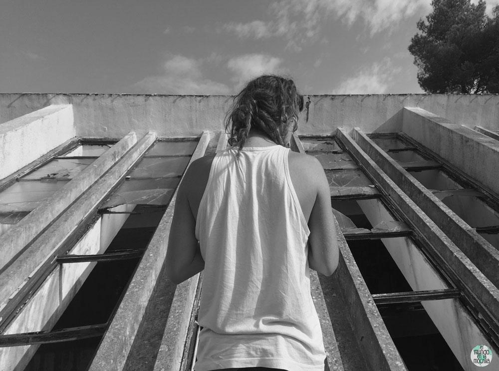 Espalda de hombre frente a ventanal roto en hotel abandonado