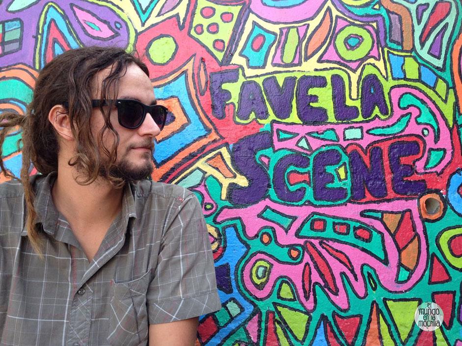 peter sobre un muro de graffiti colorido que dice favela scene en santa marta, rio de janeiro