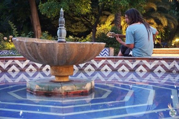 Peter tocando la guitarra tras una fuente en el Parque María Luisa en Sevilla