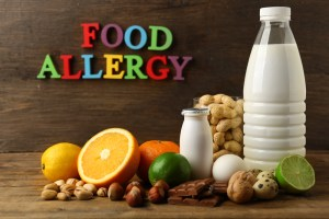 "words ""food allergy"" in background along with common food allergens on table including milk, nuts, and fruit"