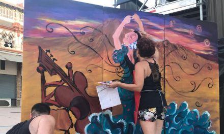 Una performance de pintura decora un mural con los artistas más representativos del Festival Internacional del Cante de las Minas