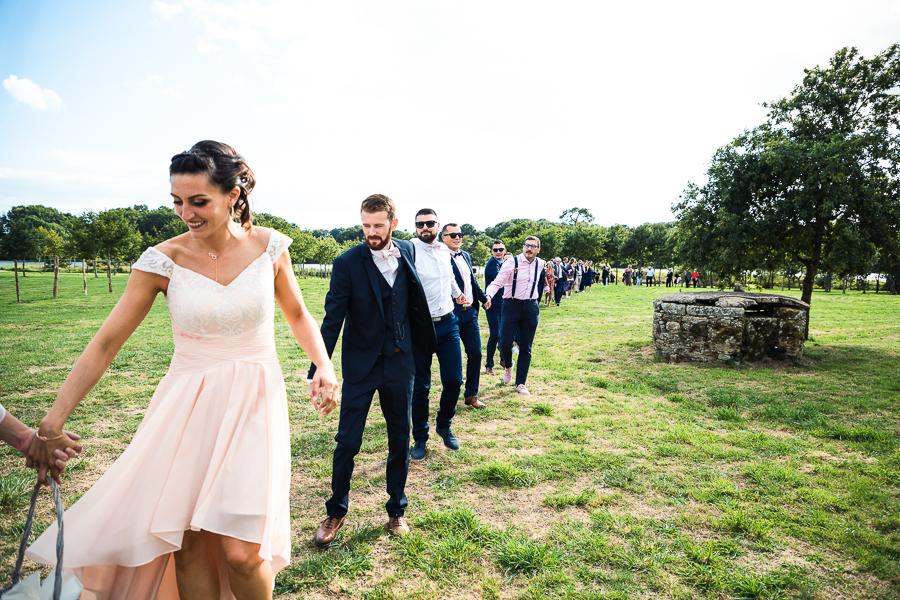 Invités sur un mariage qui avancent en se donnant la main.