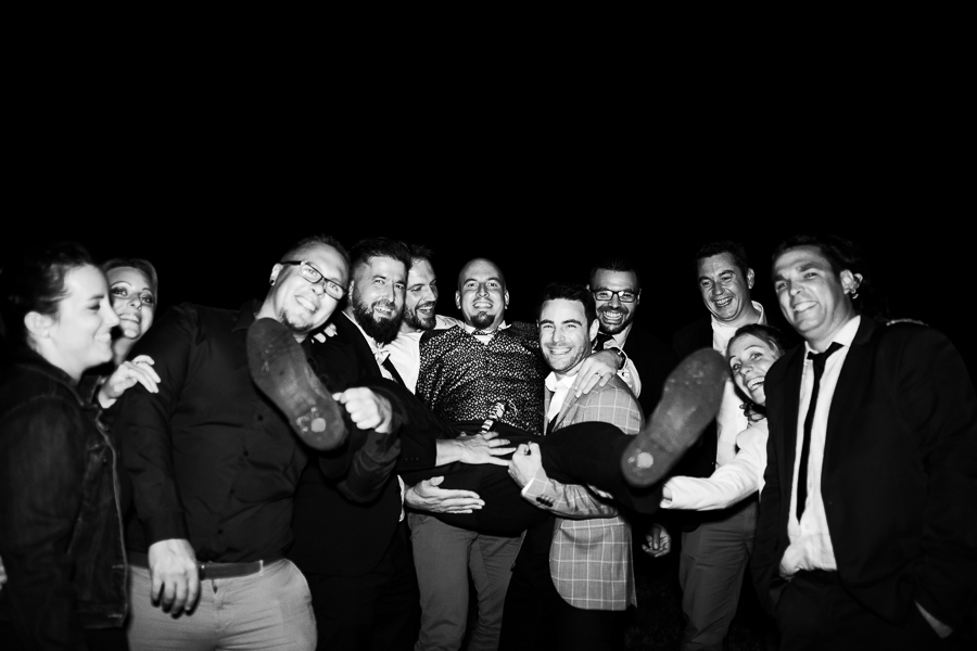 Photographie d'invités qui portent le marié.