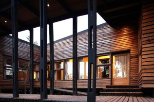 Single family house built in the middle of an orchard adopting cabin style with exposed wooden wall Casa Lo Cañas (5)