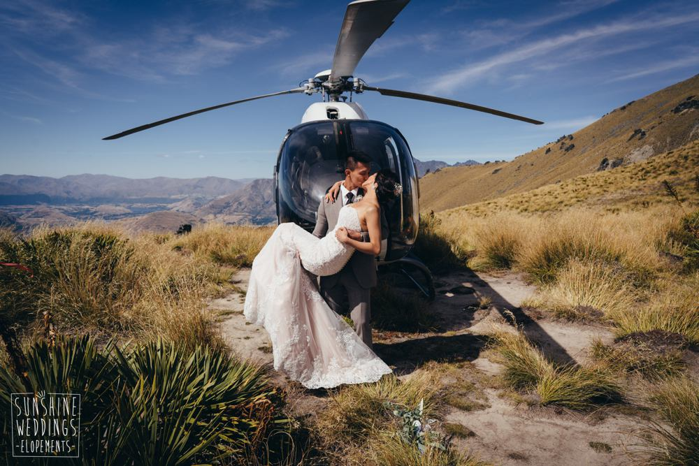 weding couple kiss on front of helicopter for elopement wedding