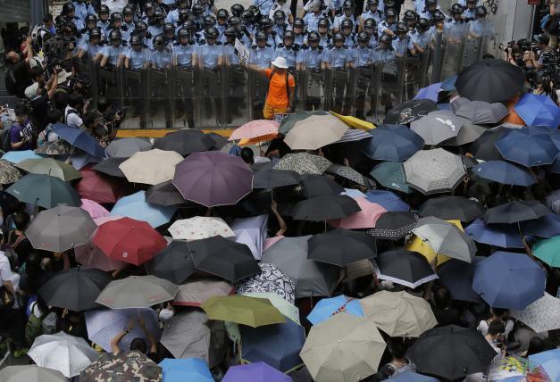 Manifestantes ante la policía durante la revolución de los paraguas. Fuente: RUSI