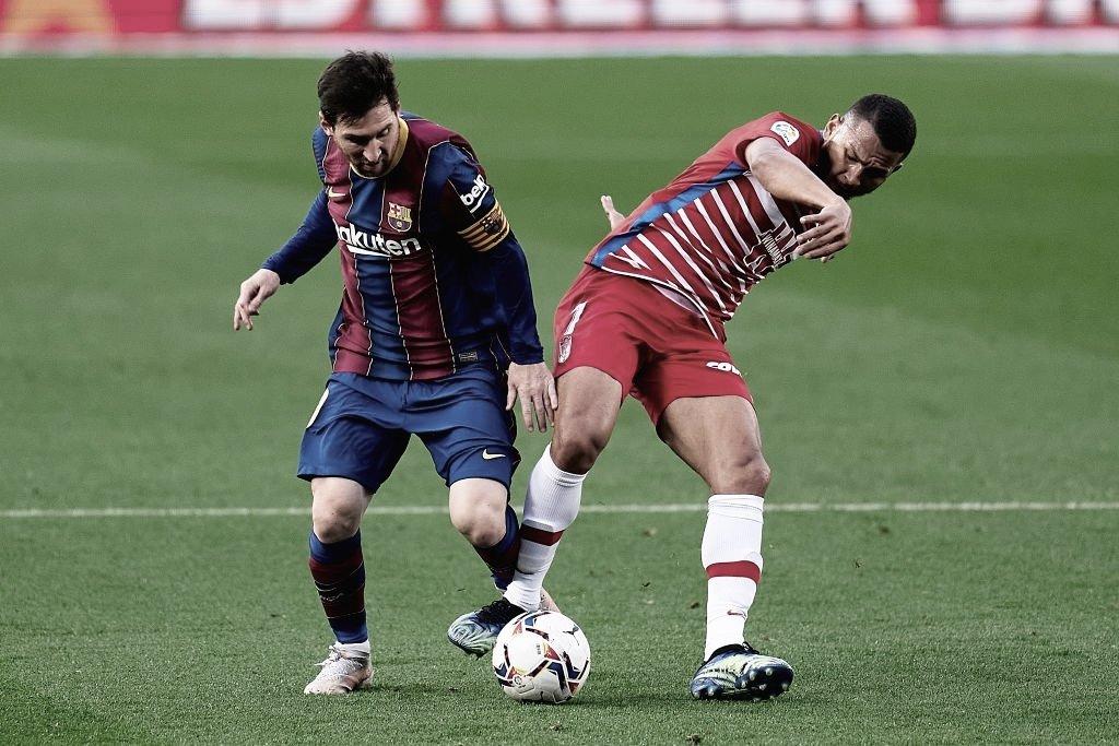 Messi intentando pasar por la dura marca de los jugadores del Granada