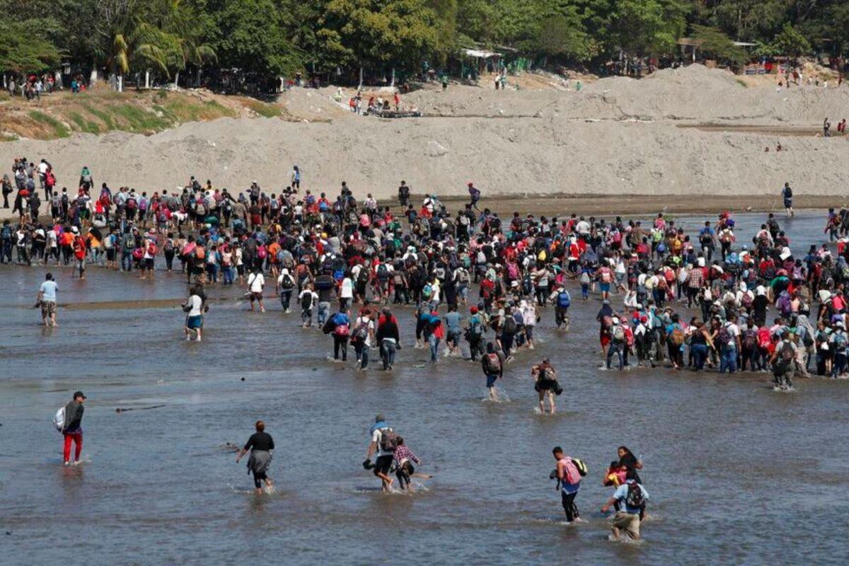 Migrantes hondureños atraviesan río para entrar a México
