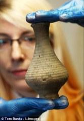Pequeño vaso cerámico en las manos de la arqueóloga. TOM BANKS ©