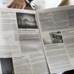 Business people reading newspaper