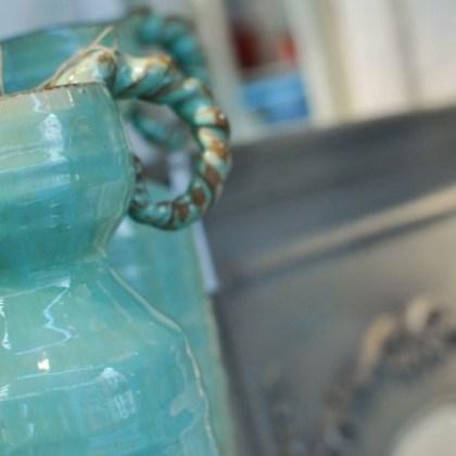 Espejo de madera estilo francés. Detalle botellas de cerámica verde agua.