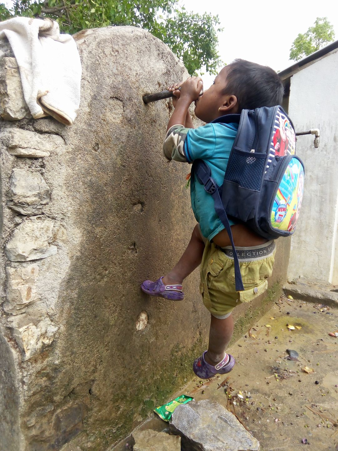 I'm very thirsty: a child in rural village attacks the tap as the tap runs out of water.