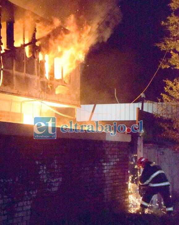 ABRIÉNDOSE PASO.- Este bombero intenta abrir con maquinaria especial un portón de metal, para ingresar a la propiedad.