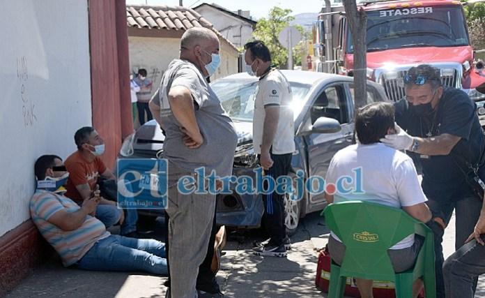 AMBOS LESIONADOS.- Recostado en una pared quedó el conductor del auto liviano, mientras que la conductora del colectivo fue atendida en una silla.