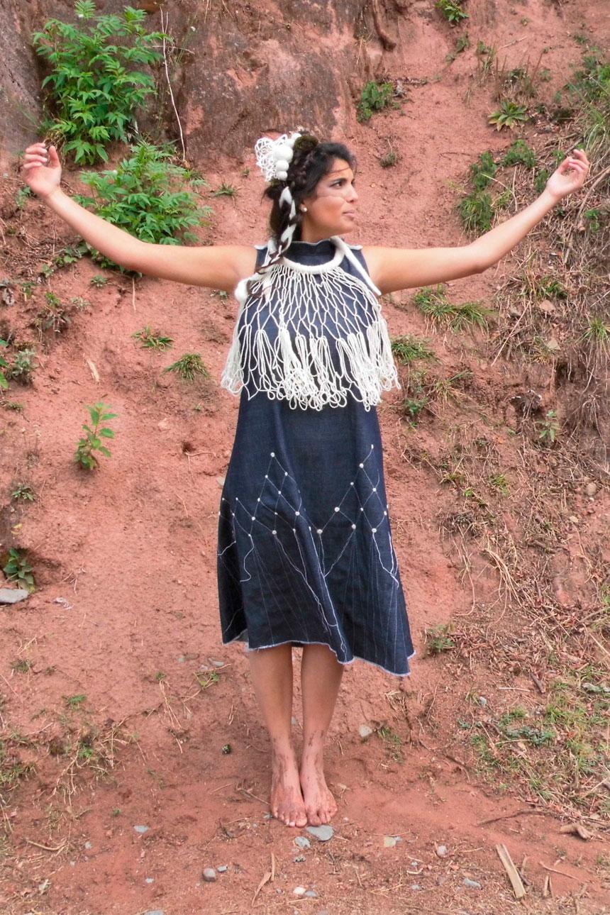 Mujer parada al aire libre, manos levantadas con vestido con adorno textil.
