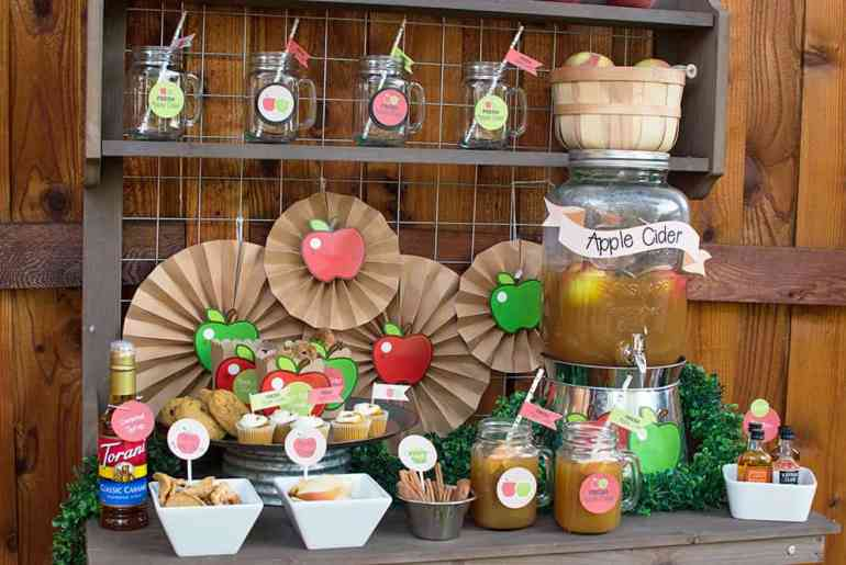 Make this Apple Cider Bar party backdrop using kraft paper fans and apple cutouts from Oriental Trading. Styling by Elva M Design Studio.
