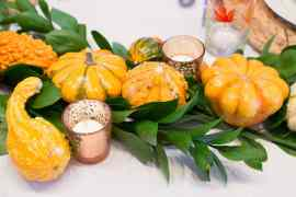 Use greenery and gourds to set a lush and vibrant Thanksgiving Table