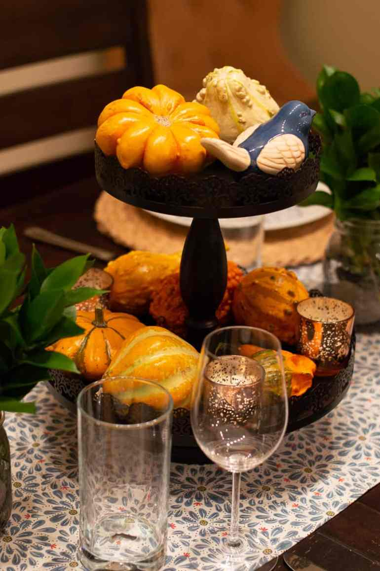 Create a lovely table centerpiece using a tiered tray, some gourds, candles, and little bird accent.