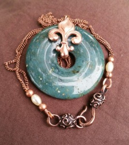 moss agate donut with red bronze fleur-de-lis, and copper chain with precosia seed beads