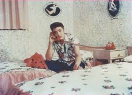 1955 or 56 Elvis in his bedroom talking on red phone with stuffed animal matching bedspread