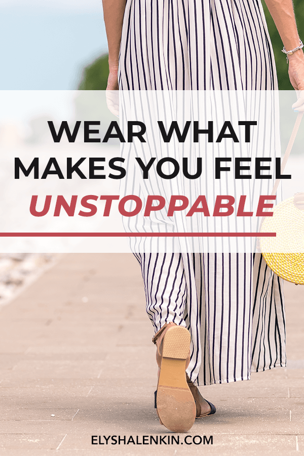 Wear what makes you feel unstoppable. Women wearing black and white striped jumpsuit walking down a path. She has a straw handbag and wear sandals.