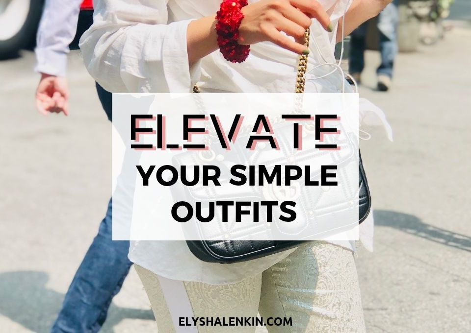Elevate your simple outfits. Women walking across the street wearing a white outfit. She has a red scrunchy around her wrist and is holding a red phone.