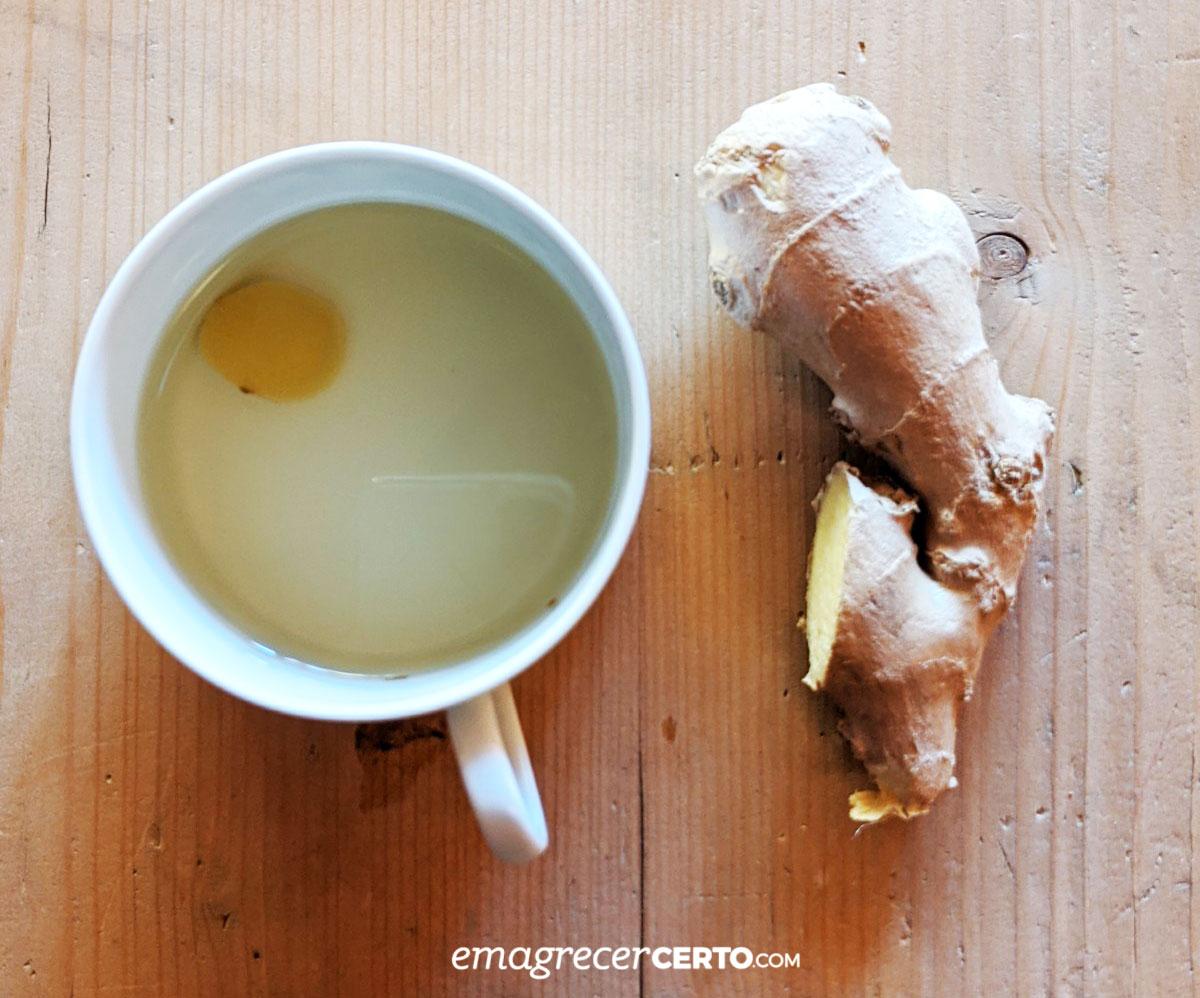 Chá de gengibre na xícara com raiz de gengibre ao lado
