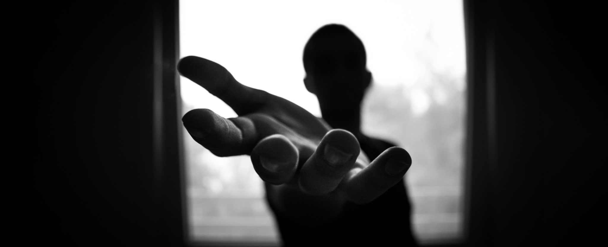 Silhouette of a person holding their hand out