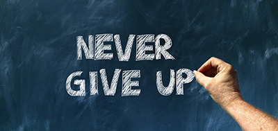 Never give up written on blackboard