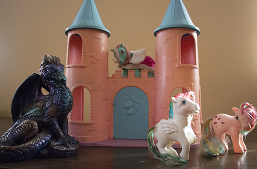 My Little Ponies standing in front of castle with large dragon