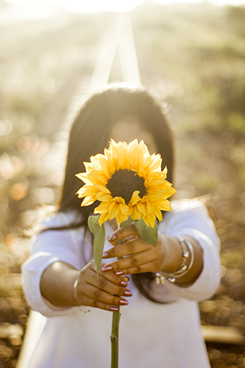 Girl standing with sunflower blocking her face