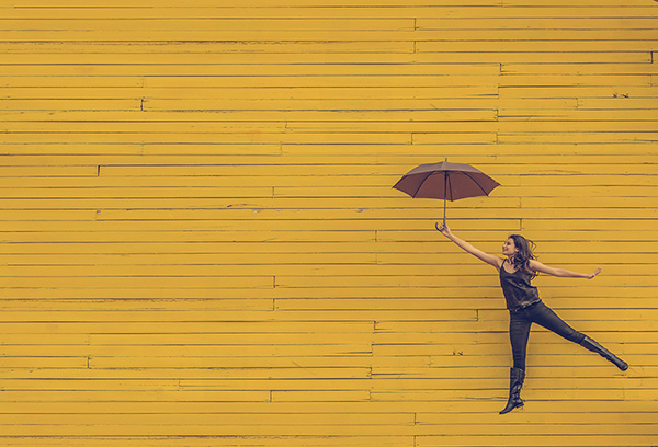 girl jumping with umbrella in front of yellow wall