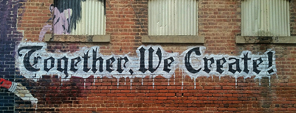 brick wall with graffiti saying Together we create