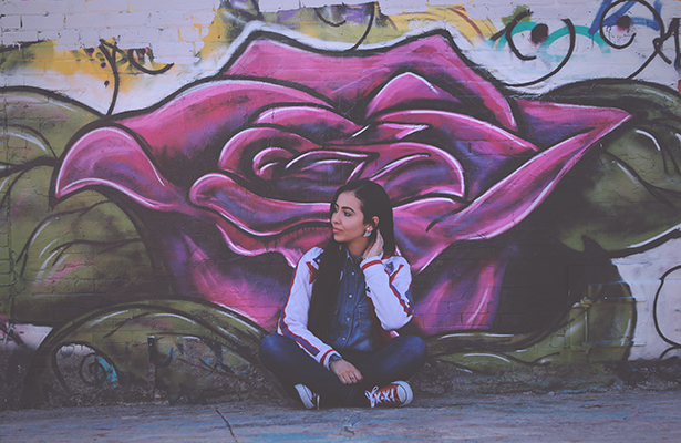 Woman sitting in front of graffiti rose