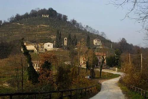 Estrada de acesso ao Santuário de Collagù e algumas residências na vizinhança.