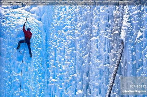 An unidentified lead ice climber tops out on frozen waterfall by a popular climbing area called Haffner Creek in Kootenay National Park, British Columbia on December 1, 2002 as its snows, Canada