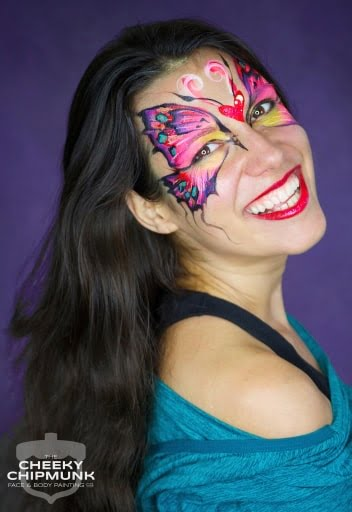 A photo of a woman with a butterfly painted around her eyes and forehead.
