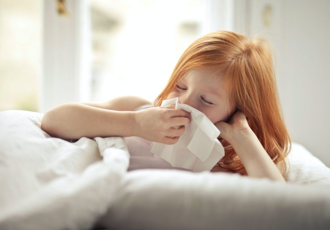 kid lying in bed blowing her nose.