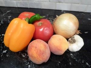 salsa veggies sitting on a counter - tomato, peach, onion, pepper, garlic