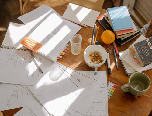 paper, notebooks, pens, bowls, and books strewn across a table