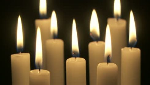 stock-footage-wide-shot-of-a-group-of-candles-burning-in-the-dark